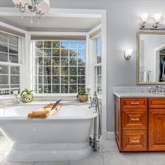 Spa-like bath with a free standing tub from Restoration Hardware, bay window, elegant lighting, sink with vanity and glass enclosed shower. Listed for $1,250,000 in Vienna, VA by The Casey Samson Team, a Wall Street Journal Top Team in Northern Virginia.