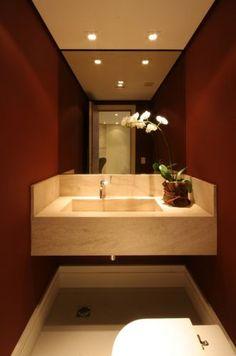 Projetado pelo escritório A8, o lavabo de 2,50 m² recebeu o piso city off white da Portobello com rodapé de madeira pintada de branco. Na parede foi aplicado tensai, uma tela com fibra de vidro, que depois foi pintada com a tinta da Coral (cor burgundy). No teto, forro de gesso liso com luminárias da Yamamura. A bancada é de limestone da Dimarmore, com cuba escupida, e os metais são da Perflex