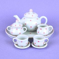 "Invite your dolls to the tea party too with a tea set that's just their size. This 10-piece miniature tea set is perfect for our 15"" doll collection and a great size for little girl's hands. This porcelain tea set is hand glazed and decorated with pink polk dots."
