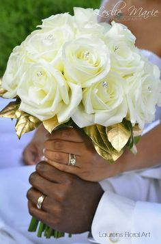 Touches of sparkling crystals are embedded in the white roses.