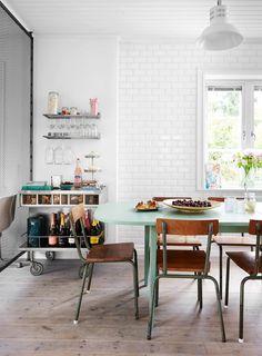 Comedor en estilo nórdico, industrial y vintage, con muebles de segunda mano. Para separar el comedor del living se colocó un panel enrejado que acentúa la estética industrial de la decoración
