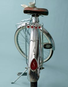 1959 Men's Schwinn Bicycle: 1950S Just as cars of the 1950s sported 2 tone shades, so did bikes, especially hues of red & cream, blue & white, black & white. Wide balloon tires, were standard & front suspension was common. Details on vintage bikes reveal their era, as evidenced by the 1959 men's Schwinn ($600) that features a teardrop reflector & four smaller ones on back rack; pedals on early '50s bikes were block-shaped while those of the late '50s to early '60s were bow-shaped.