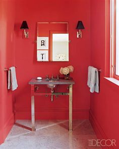 Small Space, Big Impact! This red powder room is very bold and is beautifully complimented with the Waterworks sconces, mirror, sink vanity and fittings.