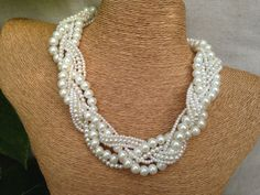 This stunning glass pearl braided necklace features 7 strands of high quality glass pearls and seed beads braided together for a true statement