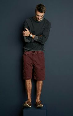 Shop this look for $95:  http://lookastic.com/men/looks/charcoal-crew-neck-sweater-and-burgundy-shorts-and-burgundy-belt-and-brown-boat-shoes/403  — Charcoal Crew-neck Sweater  — Burgundy Shorts  — Burgundy Canvas Belt  — Brown Leather Boat Shoes