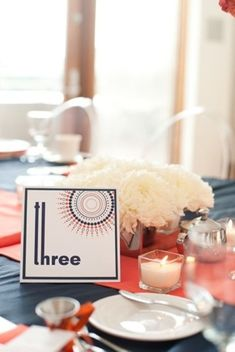 I like the idea of a colored place mat with tea light candles and a small flower centerpiece. $$$$ cheaper too