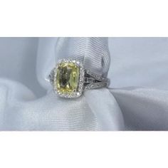 For sale, 18 kt White gold custom Ceylon sapphire ring containing a cushion cut untreated natural yellow sapphire measuring 9.75 x 7.43 x 4.83 mm weighing 3.01 carat. Type II. medium light, moderately strong, yellow color GIA Y 4/4 , set with 58 brilliant round cut diamonds with 2 baguette cut diamonds with a approximate weight .45 ct's VS - Si clarity G - H color. $4,750.00 Sapphire Ring Co. 727 797 0007.