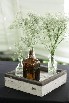 Our Rustic Centerpiece built from barn wood spruced up with doilies along the bottom. We had all of our local bars save us their empty liquor bottles and had over 200 FREE vases :)