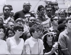 June 6, 1968: Grieving supporters of Senator Robert Kennedy watch as a hearse bearing his casket arrives near Air Force Two, at Los Angeles Airport.  The woman in the lower right is taking flash pictures of the scene.