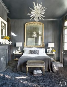 Curtains of a Sahco wool from Donghia hang in a guest room; the bedside tables are vintage Paul McCobb, and the Louis XVI–style bench is clad in a Pollack velvet.