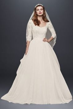 Made for the modern princess, this classic organza ball gown was designed with demure three-quarter lace sleeves and a flattering sweetheart neckline. The draping of the organza skirt adds the perfect touch of drama. Oleg Cassini, exclusively at David's Bridal. Also available in