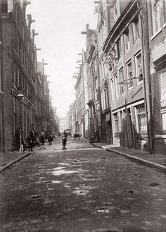 Steden. De Palmstraat in de Jordaan. Op straat staan kinderen en vrouwen met elkaar te praten. Amsterdam, Nederland, 1910.
