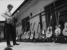 SINGER GLEN CAMPBELL POSING WITH PART OF HIS COLLECTION OF GUITARS