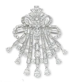 A DIAMOND BROOCH. Designed as an openwork vari-cut diamond scrolled plaque, extending baguette-cut diamond ribbons with circular-cut diamond accents and pear-shaped diamond terminals, mounted in platinum, (with pendant hoop for suspension).