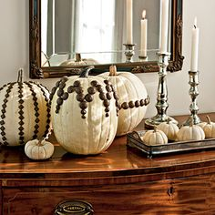 Upholstery tacks easily give a graphic look to plain white pumpkins. | SouthernLiving.com