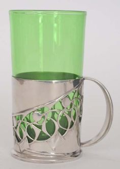Archibald Knox - Liberty & Co - A Tudric polished pewter tea glass with pierced stylised leaf and berry decoration