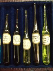 Glass tube containing 'Uranous Sulphate A,' 7.4cm long. Pale yellow liquid. From set of 12 liquids for absorption spectra in leather case with blue velvet lining. Gold logo of John Browning of London inside case. Yale Peabody Museum of Natural History