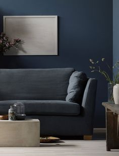 Moody shades are all the range | We're loving the juxtaposition of the light floors and dark walls with the modern coffee table and rustic wood sideboard | Daniella Witte styled an IKEA Stockholm sofa with a Bemz cover in Graphite Simply Linen