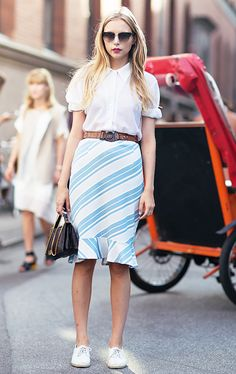 A white button-down shirt is paired with a belted striped knee-length skirt, white sneakers, and a top handle bag