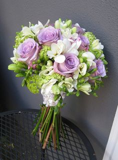 wedding bouquet light purple and green with white and lilac roses. (perhaps add a few more purple roses because I like color lol)