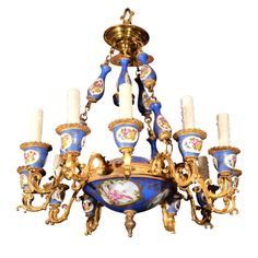 Louis XVI, Serves style Chandelier  France Mid to Late 1800's  Chandelier with Twelve Gold Ormolu Candle arms in Louis XVI, Serves Porcelain style. The Serves style scenic medallions are beautifully painted, top and bottom bowls of the fixture, with four supporting chains of painted porcelain links separated with gold ormulu links and twelve candle cups painted in the same style.