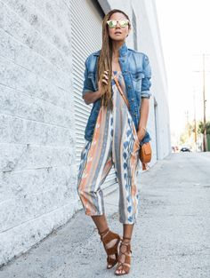 Blogger Stuff She Likes wears a printed jumpsuit, denim jacket, crossbody bag, and lace-up suede heels