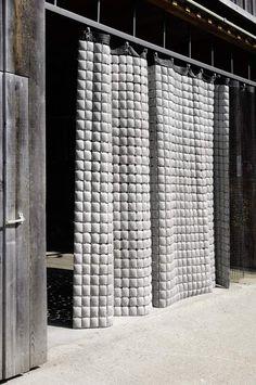 Le rideau en béton Memux est utilisable en intérieur pour délimiter un espace ou en extérieur comme élément de façade. Il développe différentes propriétés : absorbeur de sons, protection contre le vent, la lumière et la chaleur. En 2008, il a reçu la distinction « best of the best » au Reddot Design Award, dans la catégorie « Eléments de construction ». Materiaux: BFUP sur trellis métallique