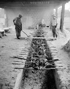 Barbequeing pork over an open pit, putting on some sauce, Braswell Plantation near Rocky Mount, NC, September 1944. From Conservation and Development Department, Travel and Tourism Photo Files, North Carolina State Archives, Raleigh, NC.