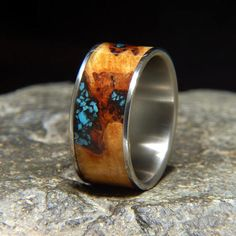 11 mm wide comfort fit titanium wedding band, with a 9 mm maple burl inlay, and sleeping beauty turquoise inlay in the natural inclusion with black fill Check out my video of this ring turning slowly in the light>