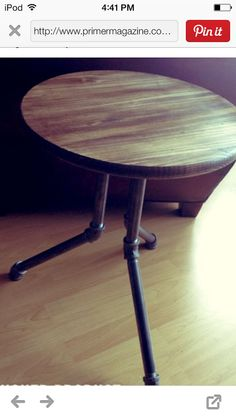 Industrial style side table with simple wood finished top and three steel pipe legs.