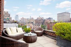 Brown woven outdoor couches with creme cushions and round coffee table with a view of New York