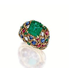 EMERALD, DIAMOND AND GEM-SET RING, MOUNTED BY CARTIER, CIRCA 1962.  Centring on a step-cut emerald weighing 4.39 carats, to a dome-shaped openwork mount embellished by circular-cut rubies, sapphires and emeralds, highlighted by brilliant-cut diamonds, mounted in 18 karat yellow gold, signed Monture Cartier.