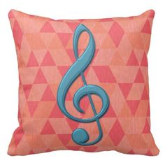 A stylish and fashionable throw pillow with a music design featuring a large treble clef in teal blue on a geometric pattern background of triangles and diamonds in shades of pink and apricot. Please note the satin raised effect of the treble clef is a printed effect, there are no raised edges on the image design.