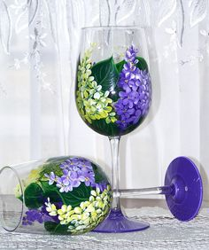A set of two 18.5 ounce long stemmed wine glasses, hand painted with purple and yellow lilacs, green leaves with a purple base. 9.25 tall