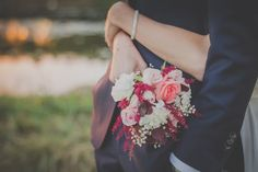 Bride holds a wedding bouquet of roses while wrapping arms around her groom Budget Wedding, Wedding Men, Wedding Planner, Wedding Gifts, Quirky Wedding, Wedding Film, Wedding Attire, Luxury Wedding, Diy Wedding