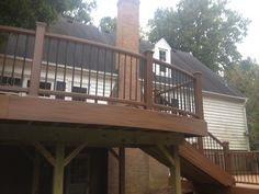 This is a large two level deck with curved decking and railing on both levels in tiki torch.  It has transcends railing in treehouse with black aluminum spindles and build in post lights.