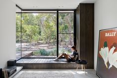 A large wood bench that looks out to the front garden through the floor-to-ceiling corner window.