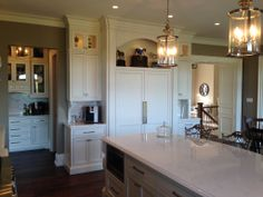 Painted face frame kitchen with fully integrated twin Sub Zero refrigerators. Notice the entrance to the butlers pantry on the left.    Like pendant lights
