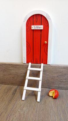 Puerta roja para el ratoncito Pérez con escalera blanca y quesitos. Todo hecho a mano por la La iluminista.