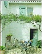 french country courtyard with suspended vine and charming outdoor setting - love the green and white. shutters on window and pike propped in corner. so cute.