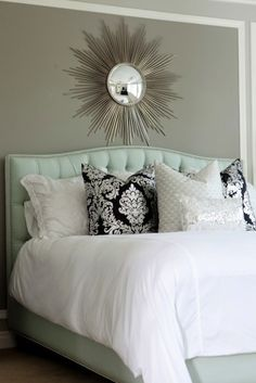 aqua headboard and sunburst mirror with black and white damask throw pillows