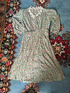 Lovely 1930s cotton feedsack dress in a dainty floral print. Gathered details on the shoulders. Crochet collar. Side snap/hook and eye closures on the left - photos 3 - 5 show the closures. Goes on over head. Such a special dress!  I could not find any flaws on this beauty, she is in