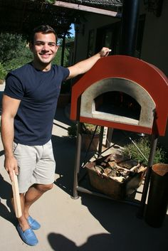A student standing next to the Mugnaini Piccolo 80 wood-fired oven on the patio at the Healdsburg, CA cooking school.