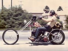 Shovelhead hardtail chopper with large rake, stretched springer, molded neck. Rider wearing leather aviator helmet.