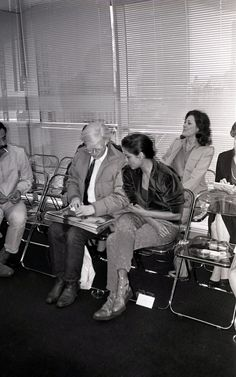 Andy Warhol, holding a stack of Interview magazine copies, sits with Bianca Jagger waiting Halston's fashion show to start in his studio. (John McDonnell)