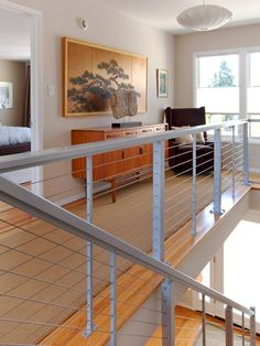 Aluminum railings with horizontal cable infill in residential interior: DesignRail® alumnum railing in residential interior landing and stair applications.