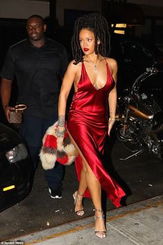 Rihanna looks ravishing in red as she flaunts her long legs and dreadlocks   There's no question that Rihanna is red hot.  But the singer looked even more ravishing than usual as she stepped out in a scarlet satin gown. Hitting the streets of New York the 28-year-old showed off her figure in the plunging gown which featured a slit to the thigh. She teamed the eye-catching halterneck dress from hot label Are You Am I with a colourful fur and a classic pair of sandals.  Keeping her make-up…