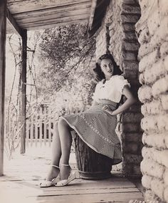 How I always pose in front of log cabins | Jinx Falkenburg | c.1944