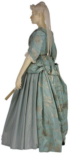 Mantua, England, ca.1720, Silver brocaded silk, lined & faced with silk. The pale blue brocaded silk is in a large-scale pattern of fantastic fruits and leaves, a typical design for the 1720s. The train of the gown is folded up & the sides held back with a loop & button. This complicated draping required a reversal of the silk when sewn together, so that only the right side of the fabric would show when properly arranged. There are 2 very large, round, heavy lead weights in each sleeve. | V