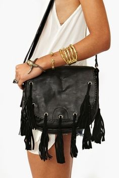 Awesome black vegan leather saddle bag featuring a jagged foldover flap with suede fringe tassels. Adjustable crossbody strap, snap c